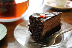 Tea Time with Chocolate Cake. Time for dessert, tea time or snack time, with a piece of chocolate cheesecake or chocolate mousse cake, with a maple leaf on top Royalty Free Stock Photography