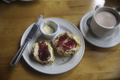 Tea Time at Clan Donald, Skye, Scotland, UK. Afternoon tea with a buttered scone with jam on top and a full cup of tea. It is in the dining room of Clan Donald Stock Image