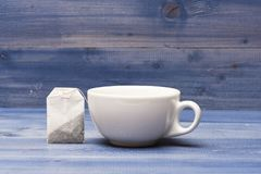 Tea time concept. Cup or white porcelain mug with transparent hot water and bag of tea. Mug filled with boiling water Stock Images