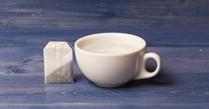 Tea time concept. Cup or white porcelain mug with transparent hot water and bag of tea. Process of tea brewing in Stock Photography