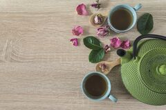 Free Tea Time Concept. Green Iron Tea Pot, Two Cup Of Tea, Rose Buds And Petals, Leaves Royalty Free Stock Images - 173436629