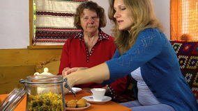Tea time cupcake in village room, woman give grandmother sugar stock video