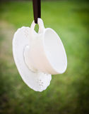 Tea Time. Dainty white teacup and saucer hanging from a ribbon stock photography