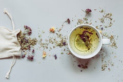 Tea time. Dry herbal tea and cup of hot tea on the gray background Royalty Free Stock Images