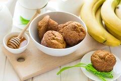 Tea time: homemade banana muffins, honey, bananas and tea settings. On white wooden table. Selective focus Royalty Free Stock Image