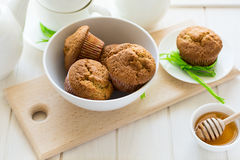 Tea time: homemade banana muffins, honey, bananas and tea settings. On white wooden table. Selective focus Stock Images