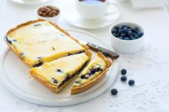 Tea time. Homemade blueberry cheesecake, cups of tea, nuts and berry. On white table cloth Royalty Free Stock Image