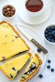 Tea time. Homemade blueberry cheesecake, cups of tea, nuts and berry. On white table cloth Stock Photography