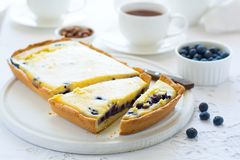 Tea time. Homemade blueberry cheesecake, cups of tea, nuts and berry. On white table cloth Stock Photos