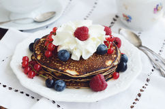 Tea time with homemade pancakes and fresh berries. Breakfast with homemade thin pancakes with whipped cream and fresh berries - raspberry, black and red currant Royalty Free Stock Photos