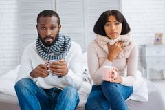Two unhealthy young people drinking tea together. Tea time. Kind lovely couple drinking hot tasty tea while staying at home and curing their sore throats stock photography