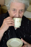 Tea time for lady. A senior woman drinking tea / coffee Stock Photography