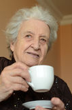 Tea time for lady. A senior woman drinking tea / coffee Stock Image