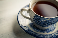 Tea Time. Photo of tea in an old fashioned porcelain cup on wooden board stock photos