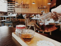 Tea time. Pouring tea from clear tea pot Stock Image