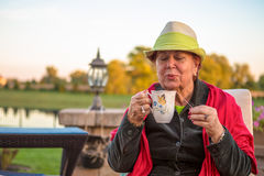 Tea Time Senior Woman Blowing her Hot Tea Royalty Free Stock Images