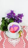 Tea time - Silver trimmed saucer and teacup filled with cutout paper hearts witting on lace doily with heart motif with purple flo. It`s tea time - Silver stock images