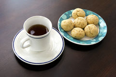 Tea time snacks. A cup of tea and a plate of yummy cookie balls made of peanut and walnut, perfect for tea time snacks Royalty Free Stock Image