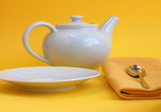 Tea Time in Spring. White tea pot, a plate and a yellow napkin with a desert spoon Stock Photography
