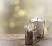 Tea time, stainless steel tea cup and teapot over wooden table o. Utdoors Stock Photos