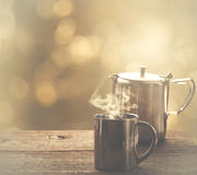 Tea time, stainless steel tea cup and teapot over wooden table o Royalty Free Stock Image