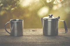 Tea time, stainless steel tea cup and teapot over wooden table o. Utdoors Royalty Free Stock Image