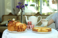 Tea time with sweet bread and muffin, apple tart and fruit. In the glass house Stock Image