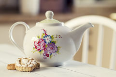 Tea time. A teapot and some biscuits. On a white wooden table Stock Photos