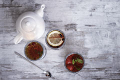 Tea Time. Three glasses of tea and teapot on a wooden table Royalty Free Stock Photo