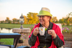 Tea Time to Stay Warm, Senior Lady with her Hot Tea. Senior woman with a straw green hat, sitting at the patio and showing her hot tea, perhaps she wants to stay Royalty Free Stock Images