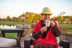 Tea Time to Stay Warm, Senior Lady with her Hot Tea. Senior woman with a straw green hat, sitting at the patio and showing her hot tea, perhaps she wants to stay Stock Photo