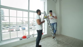 Tea time. Two workers break and snack after make repairs in a new apartment. A Man takes the paint to another man on the ladder stock video
