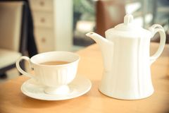 Tea time. A white cup of tea and a jug on a table / Tea time concept Royalty Free Stock Photos