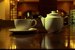 Tea time. White teacup and teapot on the wooden table in dark room, side view Stock Photos