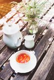 Tea time on wooden table in cottage garden. Vintage color filter Royalty Free Stock Photography