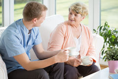 Tea time. Young handsome male nurse and senior women during tea time Royalty Free Stock Photos