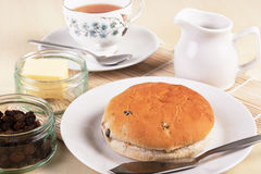 Tea with a traditional British teacake of raisins Royalty Free Stock Image