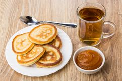 Tea in transparent cup, pancakes, bowls with apricot jam Stock Image
