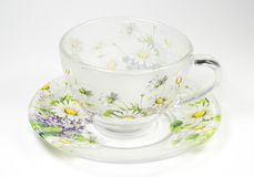 Tea transparent cup on a saucer with an ornament. From green colours stock photography
