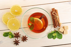 Tea in a transparent mug with lemon and cinnamon and mint leaves Stock Photo