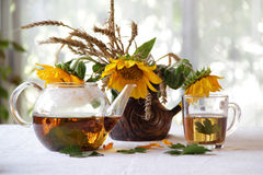 Tea in a transparent teapot and sunflowers in a ceramic vase Royalty Free Stock Photography