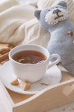 Tea tray and sweater. White wood background, toned Stock Images