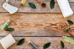 Tea tree spa composition. Fresh tea tree leaves, natural cosmetics, towel on rustic wooden background top view copy. Tea tree spa composition. Fresh tea tree stock images