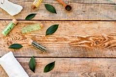 Tea tree spa composition. Fresh tea tree leaves, natural cosmetics, towel on rustic wooden background top view copy. Tea tree spa composition. Fresh tea tree stock photography