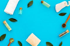 Tea tree spa composition. Fresh tea tree leaves, natural cosmetics, towel on blue background top view space for text stock photos