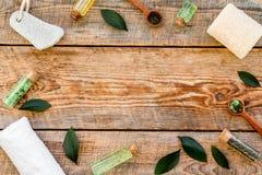 Tea tree spa composition. Fresh tea tree leaves, natural cosmetics, towel on rustic wooden background top view copy. Tea tree spa composition. Fresh tea tree stock image