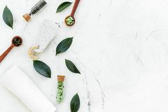 Tea tree spa composition. Fresh tea tree leaves, natural cosmetics, towel on white stone background top view copy space stock image