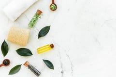 Tea tree spa composition. Fresh tea tree leaves, natural cosmetics, towel on white stone background top view copy space. Tea tree spa composition. Fresh tea tree royalty free stock photo