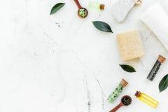 Tea tree spa composition. Fresh tea tree leaves, natural cosmetics, towel on white stone background top view copy space. Tea tree spa composition. Fresh tea tree stock photography