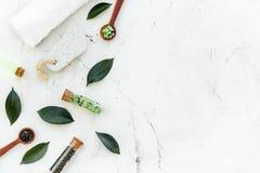 Tea tree spa composition. Fresh tea tree leaves, natural cosmetics, towel on white stone background top view copy space. Tea tree spa composition. Fresh tea tree stock image